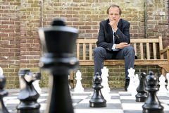 Thinking Man Sitting At A Life Sized Outdoor Chess Board Stock Image