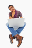 Thinking man sitting on floor using laptop Royalty Free Stock Photos