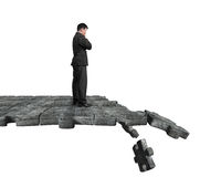 Thinking man standing on breaking puzzle ground Royalty Free Stock Image