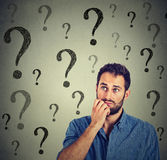 Thinking man wondering looking up has many questions. Thinking business man wondering looking up has many questions isolated on gray wall background Royalty Free Stock Image