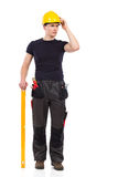 Thinking manual worker with a measuring instrument. Manual worker posing with a measuring tool and thinking. Full length studio shot isolated on white Royalty Free Stock Photo
