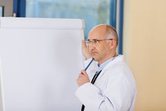 Thinking Mature Doctor Standing Near Flipchart Royalty Free Stock Images