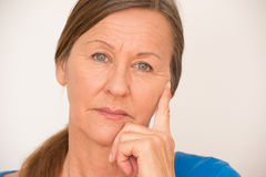 Thinking mature woman serious look Stock Photo