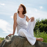 Thinking mature yoga woman relaxing outdoors. Senior zen - thinking 50s woman sitting on a stone for outdoors yoga session wearing white seeking serenity and Royalty Free Stock Photo