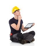 Thinking mechanic with a digital tablet. Portrait of thinking manual worker holding digital tablet and sitting on a floor. Full length studio shot isolated on Royalty Free Stock Photos