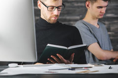 Thinking men doing paperwork. Portrait of thinking european men doing paperwork at desk with devices, supplies and other items. Teamwork and project concept Royalty Free Stock Photos