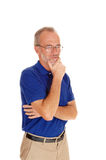 Thinking middle age male with hand on chin. A waist up image of a middle age man in a blue t-shirt standing isolated Stock Photo