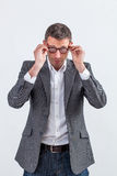 Thinking middle aged businessman adjusting his eyeglasses to read royalty free stock photography