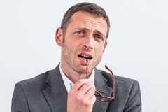 Thinking middle aged businessman biting his eyeglasses expressing doubt Royalty Free Stock Photos