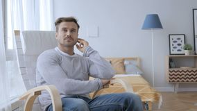 Thinking middle aged man sitting on casual chair, brainstorming stock footage