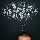 Thinking about money. A man over a blackboard with a thought bubble drawn in it and a pile of dollar signs in it Royalty Free Stock Photo