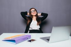 Thinking office worker day dreaming looking up smiling happy. Young business woman in suit sitting at office desk with laptop. stock photo