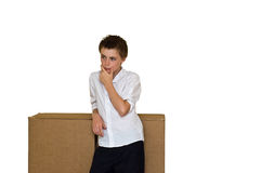 Thinking outside the box. An image of a dishevelled young teen stood thinking outside a large cardboard box, depicting the common phrase thinking outside of the stock photo