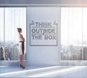 Thinking outside the box. Businesswoman looking outside of window in empty interior with sketch on wall. Concept of thinking outside the box. 3D Rendering Royalty Free Stock Photography