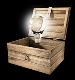 Thinking Outside The Box Lightbulb. An open rough wooden planked box with a hinged lid and a hasp with a regular illuminated lightbulb above it on an  background Royalty Free Stock Images