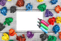Thinking outside the box. Multicolored crumpled sheets of paper and blank sheet of paper with colorful felt pens. stock image