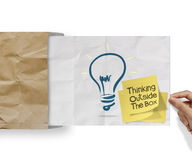 Thinking outside the box on sticky note and lightbulb as creative on crumpled envelope paper. Concept stock photos