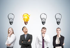 Thinking people and light bulbs, gray wall. Portrait of two men and two women thinking about business near a gray wall. Light bulbs are drawn above their heads Royalty Free Stock Photo