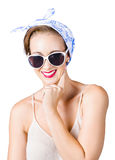 Smiling pin-up girl. Attractive smiling woman posing as thinking pin-up  girl with blue and white head scarf and sunglasses isolated on white background Royalty Free Stock Images