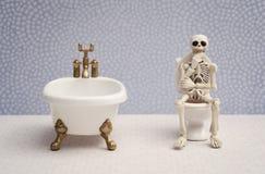 Thinking pose skeleton. Skeleton sitting on water closet while thinking royalty free stock photo