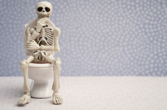 Thinking pose skeleton. Skeleton sitting on water closet while thinking stock images