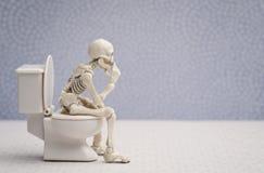 Thinking pose skeleton. Skeleton sitting on water closet while thinking stock photo
