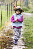 Thinking preschooler walking on garden path with shovel on shoulder Stock Photography