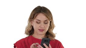 Thinking pretty blonde sending a text on her phone on white background. stock video footage