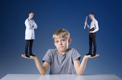 Thinking about profession. Little confused boy thinking about his future profession Stock Photo
