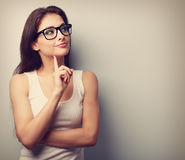 Thinking professional woman in glasses looking with finger under. The face on empty space background. Vintage portrait royalty free stock image