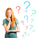 Unknowing. Thinking red-haired girl isolated on a white, questions marks at background Stock Images