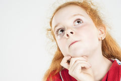 Thinking Red-haired Girl Looking Up and Touching Chin Royalty Free Stock Images