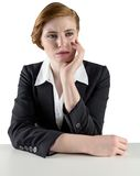 Thinking redhead businesswoman sitting at desk Stock Image