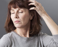 Thinking 50's woman concerned about her skin and hair quality Stock Photography