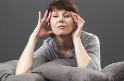 Thinking 50's woman lifting her eyes for soft facial contour Stock Photos