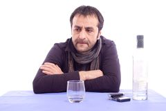 Thinking sad looking man. Sitting at the table isolated on white background Royalty Free Stock Images