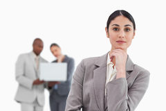 Thinking saleswoman with colleagues behind her Royalty Free Stock Photo