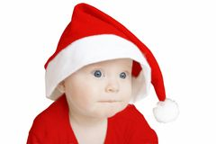 Thinking santa. Pensive baby in big Santa Claus hat on white background Royalty Free Stock Images
