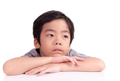 Thinking schoolchild sitting at desk Royalty Free Stock Images
