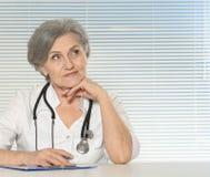 Thinking senior doctor woman Stock Image