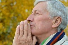 Thinking senior man praying. Portrait of thoughtful elderly man praying on yellow autumn background royalty free stock photography