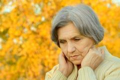 Thinking senior woman. Portrait of thinking senior woman in autumn park Royalty Free Stock Photo