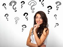 Thinking smiling with hand under the face woman with many drawing creative question marks above the head on white background royalty free stock photos