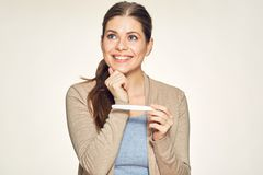 Thinking smiling woman holding pregnant test. Isolated portrait royalty free stock photos