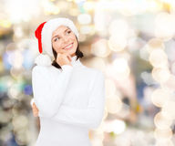 Thinking and smiling woman in santa helper hat Stock Photography