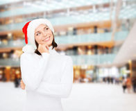 Thinking and smiling woman in santa helper hat Stock Photos