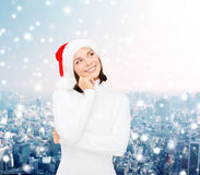 Thinking and smiling woman in santa helper hat Stock Image