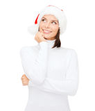 Thinking and smiling woman in santa helper hat Royalty Free Stock Image