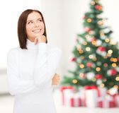 Thinking and smiling woman in white sweater Royalty Free Stock Images