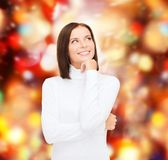 Thinking and smiling woman in white sweater Stock Image